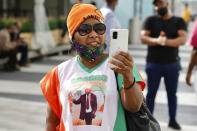 A supporter of former Ivory Coast President Laurent Gbagbo takes photos with her smartphone at the Brussels international airport in Brussels, Thursday, June 17, 2021. The former Ivory Coast president Laurent Gbagbo is returning home to Ivory Coast for the first time in nearly a decade, after his acquittal on war crimes charges was upheld at the International Criminal Court earlier this year. (AP Photo/Olivier Matthys)