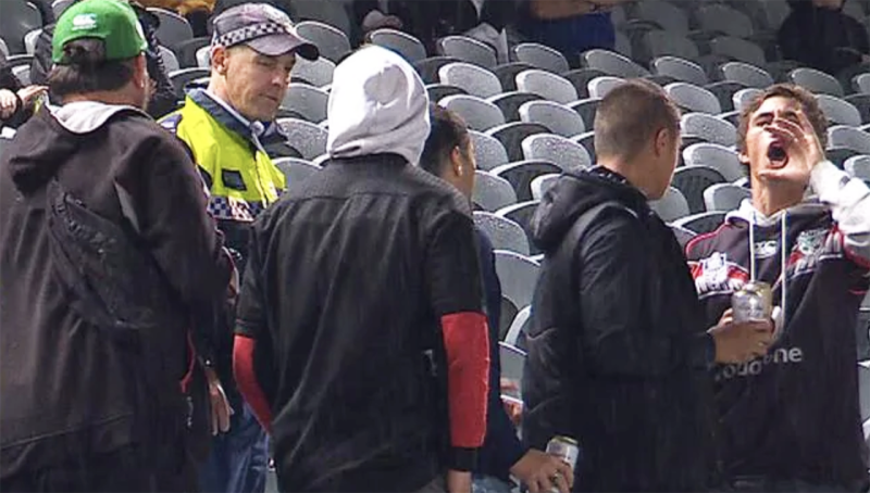A police officer is seen escorting a group of people from Central Coast Stadium, who are believed to have racially abused Penrith player Brent Naden.
