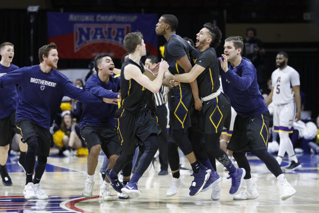Graceland's Justin Harley, center, celebrates his game-winning overtime basket with Dalton Payton, left, Waseem Limbada, right, and other teammates in the NAIA men's championship college basketball game Tuesday, March 20, 2018, in Kansas City, Mo. Graceland defeated LSU Alexandria 83-80. (AP Photo/Colin E. Braley)