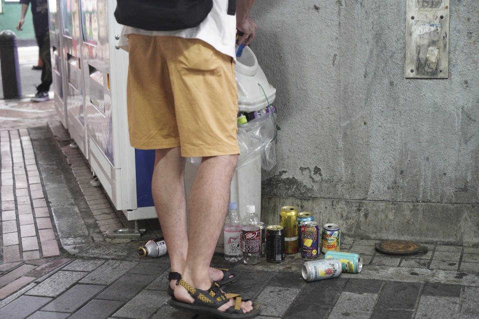 A young man throws a beer can to already full garbage box in Tokyo's Shinjuku district Monday, July 19, 2021. The latest state of emergency has asked restaurants and bars to close by 8 p.m., if not entirely. This has pushed people to drink outside, although many bars remain open and bustling with customers who are defying the rules and expressing frustration and indifference. (AP Photo/Kantaro Komiya)