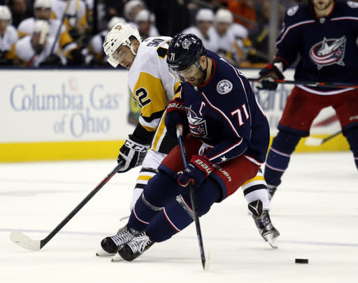 Columbus Blue Jackets forward Nick Foligno, right, works against Pittsburgh Penguins forward Dominik Simon, of the Czech Republic, during the first period of an NHL hockey game in Columbus, Ohio, Saturday, March 9, 2019. (AP Photo/Paul Vernon)