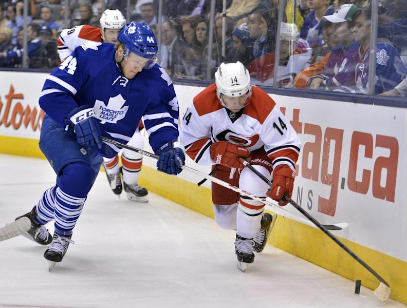 Toronto Maple Leafs' Morgan Rielly, left, and Carolina Hurricanes' Nathan Gerbe compete along the boards during the first period of an NHL hockey game in Toronto on Thursday, Oct. 17, 2013. (AP Photo/The Canadian Press, Nathan Denette)