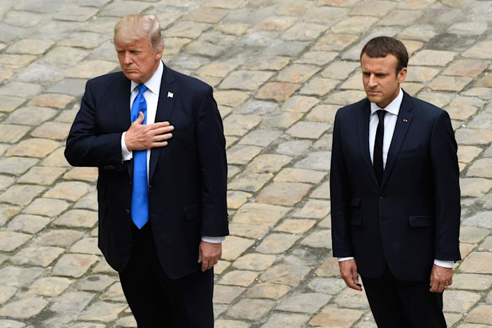 Trumpand French President Emmanuel Macron stand during the US and French national anthems.