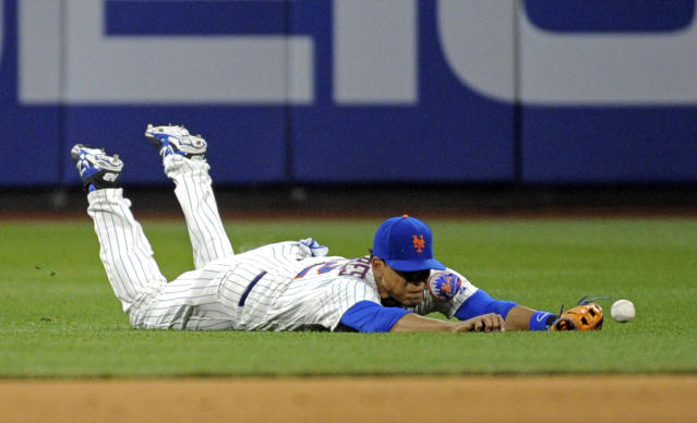 New York Mets center fielder Juan Lagares cannot catch a ball hit by Philadelphia Phillie' Domonic Brown for an RBI-single during the first inning of a baseball game on Saturday, May 10, 2014, at Citi Field in New York. (AP Photo/Bill Kostroun)