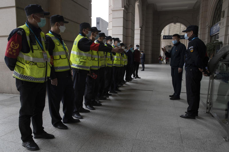 Security personnel are briefed at the Hankou railway station on the eve of its resuming outbound traffic in Wuhan in central China's Hubei province on Tuesday, April 7, 2020. Chinese authorities are moving to lift an 11-week lockdown of Wuhan, allowing residents to once again travel in and out of the sprawling city where the coronavirus pandemic began. (AP Photo/Ng Han Guan)