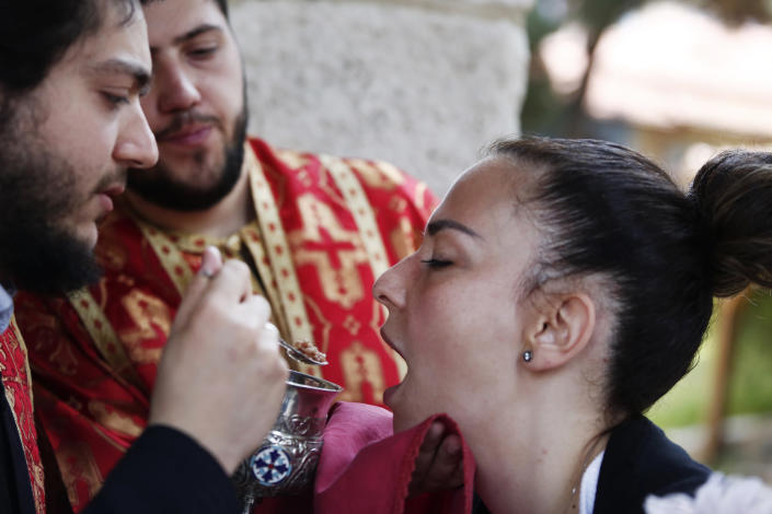 In this Sunday, May 24, 2020, photo, a Greek Orthodox priest distributes Holy Communion during Sunday Mass at a church, in the northern city of Thessaloniki, Greece, using a traditional shared spoon. Contrary to science, the Greek Orthodox Church insists it is impossible for any disease, including the coronavirus, to be transmitted through Holy Communion. (AP Photo/Giannis Papanikos)