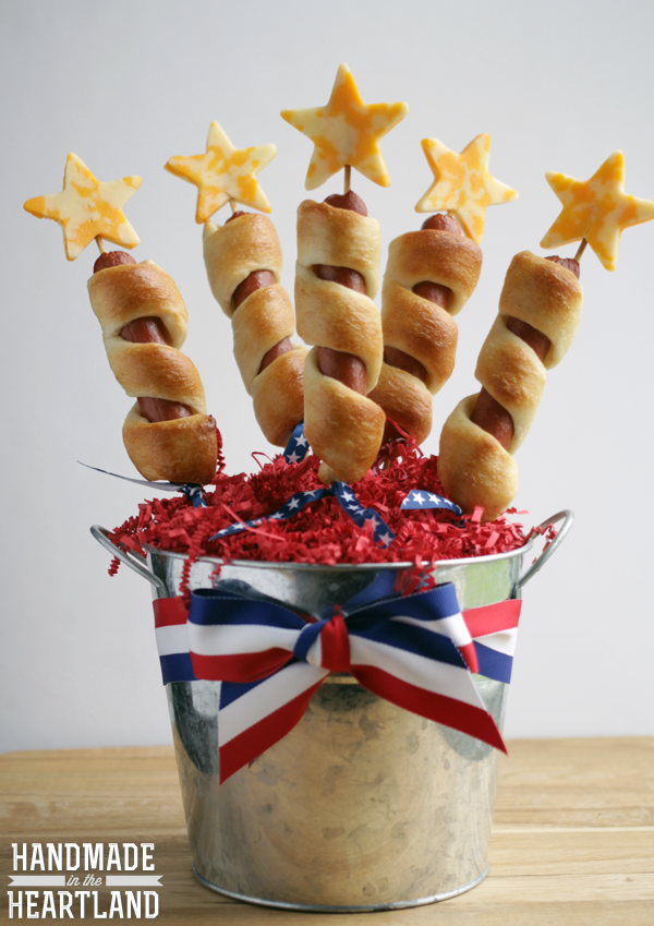 """<p>Wrap hot dogs in flaky dough and top with cheese stars for a fun and festive appetizer. </p><p><strong>Get the recipe at <a href=""""http://www.handmadeintheheartland.com/2014/06/4th-of-july-firecracker-dogs.html"""" rel=""""nofollow noopener"""" target=""""_blank"""" data-ylk=""""slk:Homemade in the Heartland"""" class=""""link rapid-noclick-resp"""">Homemade in the Heartland</a>.</strong> </p>"""