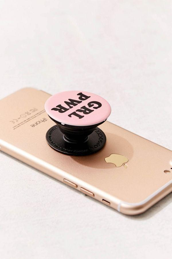 """<p>There's a very important message under your phone with the <a href=""""https://www.popsugar.com/buy/PopSockets-GRL-PWR-Phone-Stand-551360?p_name=PopSockets%20GRL%20PWR%20Phone%20Stand&retailer=popsockets.com&pid=551360&price=10&evar1=fab%3Aus&evar9=43276316&evar98=https%3A%2F%2Fwww.popsugar.com%2Fphoto-gallery%2F43276316%2Fimage%2F45862912%2FPopSockets-GRL-PWR-Phone-Stand&list1=shopping%2Cfeminism%2Cpopsockets&prop13=api&pdata=1"""" rel=""""nofollow"""" data-shoppable-link=""""1"""" target=""""_blank"""" class=""""ga-track"""" data-ga-category=""""Related"""" data-ga-label=""""https://www.popsockets.com/p/grl-pwr/13-000256.html?lang=en_US"""" data-ga-action=""""In-Line Links"""">PopSockets GRL PWR Phone Stand</a> ($10).</p>"""