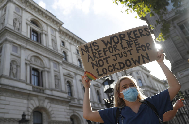 Demonstrators, a number of them nurses and care workers from St Thomas' Hospital, hold placards as they protest for a pay rise in London, Wednesday, July 29, 2020. Heath care unions are launching a campaign for a pay rise for NHS nurses and care workers. (AP Photo/Alastair Grant)