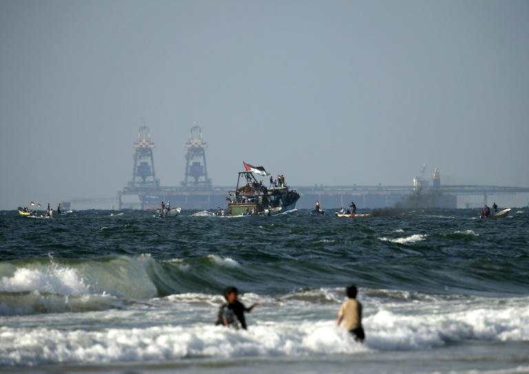 Palestinian boats participate in a protest against the more than a decade-long blockade of Gaza on August 11, 2018 with Israel's Rutenberg power station seen in the background
