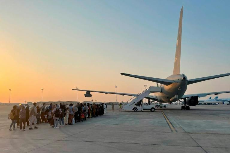 A handout picture released by the Italian Defence press office on August 21, 2021 and taken on August 20, 2021 shows passengers who fled Afghanistan boarding on an Italian military aircraft at Kuwait International Airport, to fly to Rome Fiumicino