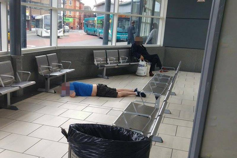 A man was pictured sprawled on the floor of a bus station (Gavin Rodda )