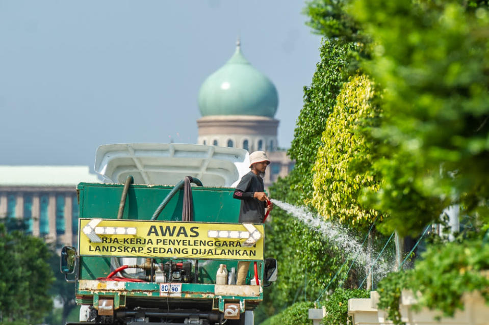A landscape worker is seen watering plants at Putrajaya Boulevard February 18, 2021. — Picture by Shafwan Zaidon
