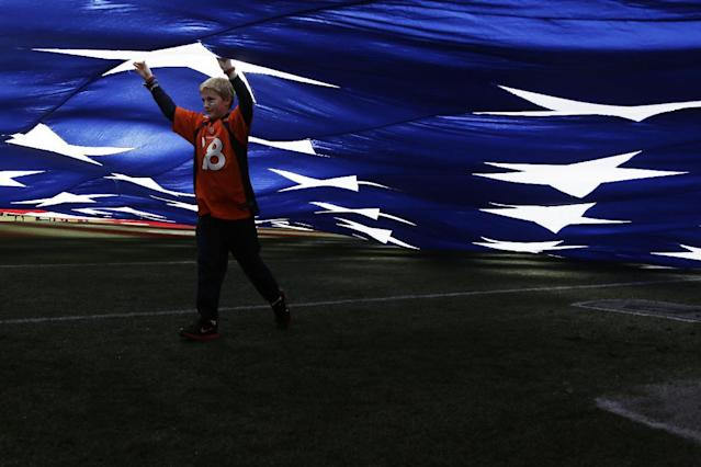 A young boy walks underneath an over-sized American flag before an NFL football game between the Denver Broncos and the New England Patriots in Denver, Md., Sunday, Jan. 19, 2014. (AP Photo/Julie Jacobson)