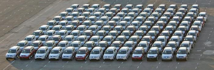 Cars parked in neat rows in a parking lot.