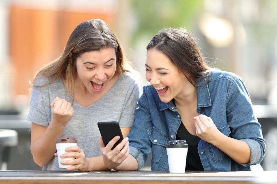 Two women celebrate lottery win while on a smartphone.