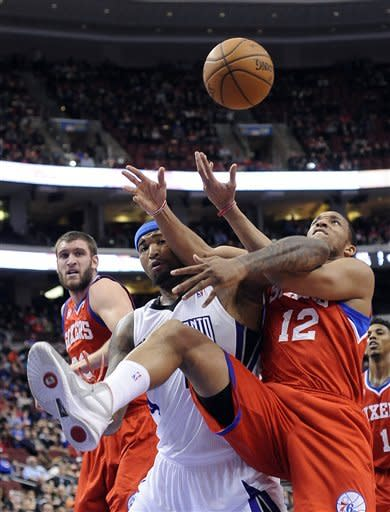 Philadelphia 76ers' Evan Turner (12) pulls in a rebound over Sacramento Kings' DeMarcus Cousins (15) during the first half of an NBA basketball game, Friday, Feb. 1, 2013, in Philadelphia. (AP Photo/Michael Perez)