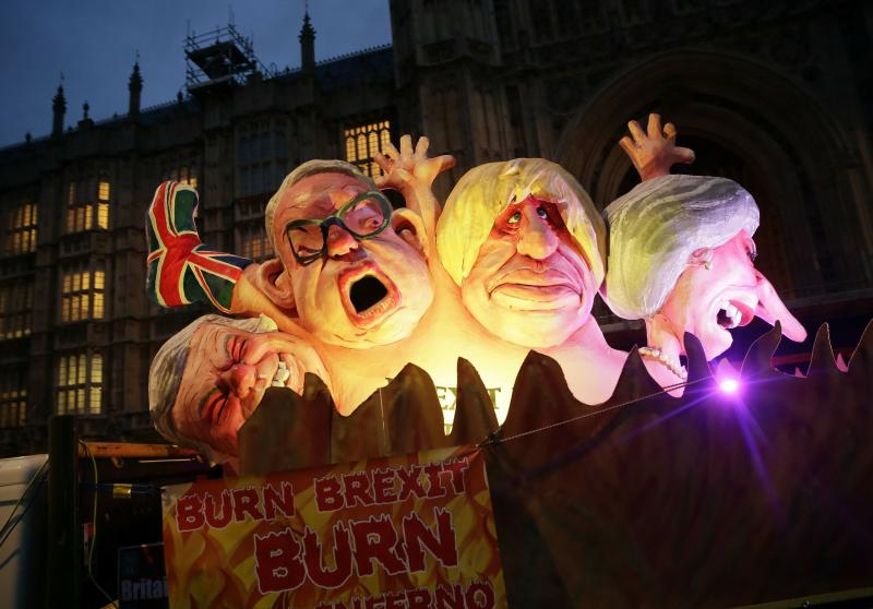 Effigies of British politicians from right, Prime Minister Theresa May, Boris Johnson and Michael Give are driven on a truck by anti-Brexit, remain in the European Union supporters outside the House of Parliament in London, Wednesday, March 13, 2019. Britain's Parliament will vote later Wednesday on whether to rule out leaving the EU on March 29 without a deal. (AP Photo/Tim Ireland)