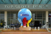 In this Wednesday, Aug. 26, 2020, file photo, the Top Glove Tower icon stand outside its headquarters in Shah Alam outside Kuala Lumpur, Malaysia. Malaysia's Top Glove Corp., the world's largest rubber glove maker, said Tuesday it expects a delay in deliveries after it was hit by a coronavirus outbreak that affected thousands of workers. (AP Photo/Vincent Thian)