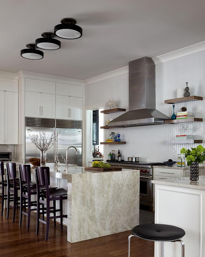 """The spacious eat-in kitchen of the newly built house didn't need a major renovation. Liss simply changed some of the cabinet hardware and added new flush-mounted fixtures from <a href=""""https://urbanelectric.com"""" rel=""""nofollow noopener"""" target=""""_blank"""" data-ylk=""""slk:Urban Electric Company"""" class=""""link rapid-noclick-resp"""">Urban Electric Company</a>. The Astania bar stools are from <a href=""""https://www.espasso.com/collection/29"""" rel=""""nofollow noopener"""" target=""""_blank"""" data-ylk=""""slk:Espasso"""" class=""""link rapid-noclick-resp"""">Espasso</a>."""