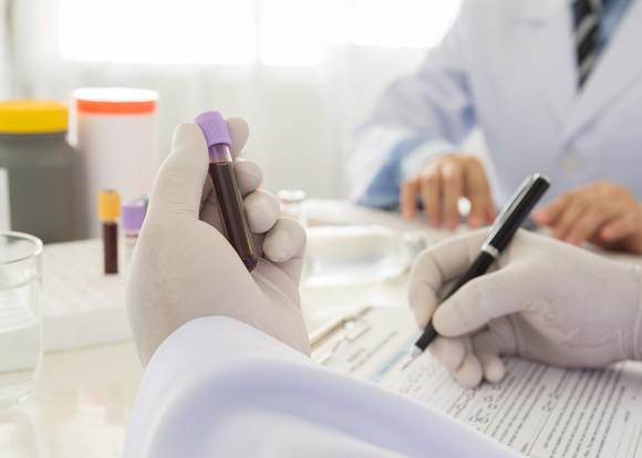 A biotech lab researcher wearing gloves while examining a vile of blood and taking notes.