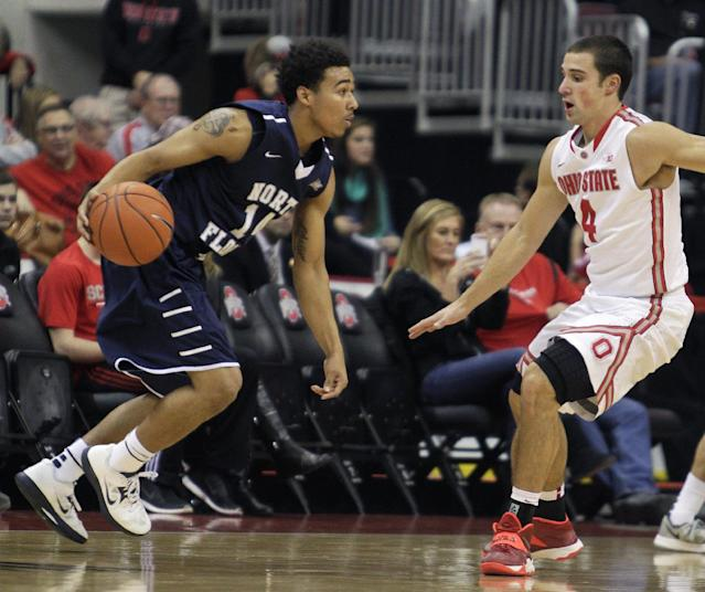 North Florida's Dallas Moore, left, tries to dribble past Ohio State's Aaron Craft during the first half of an NCAA college basketball game on Friday, Nov. 29, 2013, in Columbus, Ohio. Ohio State won 99-64. (AP Photo/Jay LaPrete)