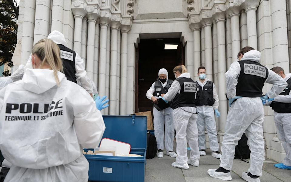 Forensic specialists inspect the scene of a reported knife attack at Notre Dame church in Nice - ERIC GAILLARD/REUTERS
