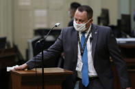 FILE — In this Monday June 15, 2020 file photo an Assembly Sargent-at-Arms wears a face mask as he disinfects the podium between use by Assembly members at the Capitol in Sacramento, Calif. California will require state employees and all health care workers to show proof of COVID-19 vaccination or get tested weekly in an effort to slow the rising coronavirus infections, mostly among the unvaccinated. The new rule will take effect next month. (AP Photo/Rich Pedroncelli, File)