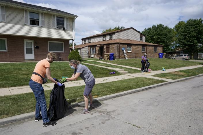 Church volunteers help clean up the neighborhood where Jacob Blake was shot last Sunday on Saturday, Aug. 29, 2020, in Kenosha, Wis. Family members of Jacob Blake, a Black man who was paralyzed after a Kenosha police officer shot him in the back, are leading a march and rally Saturday to call for an end to police violence. (AP Photo/Morry Gash)