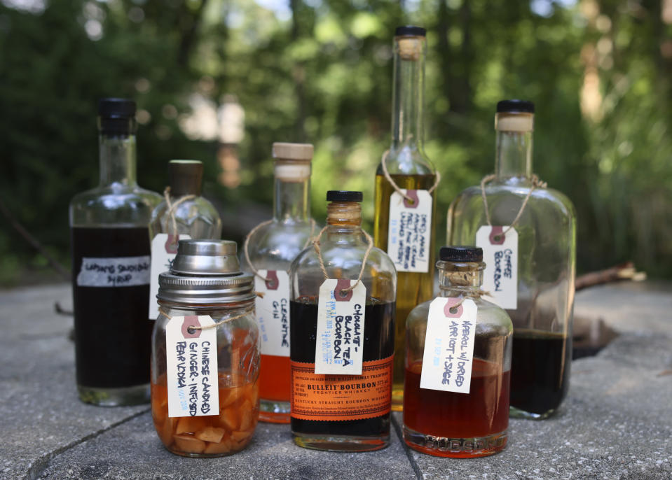A group of bottled alcohol and syrup infusions appear at the edge of a fire pit in Allison Park, Pa., on July 4, 2021. Alcohol and syrup infusions are growing in popularity and are relatively simple to incorporate into home bars. (AP Photo/Ted Anthony)