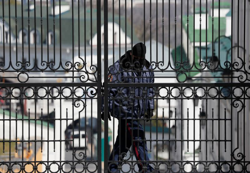 A security guard wearing a protective face mask is seen at the gate of Kiev Pechersk Lavra monastery in Kiev