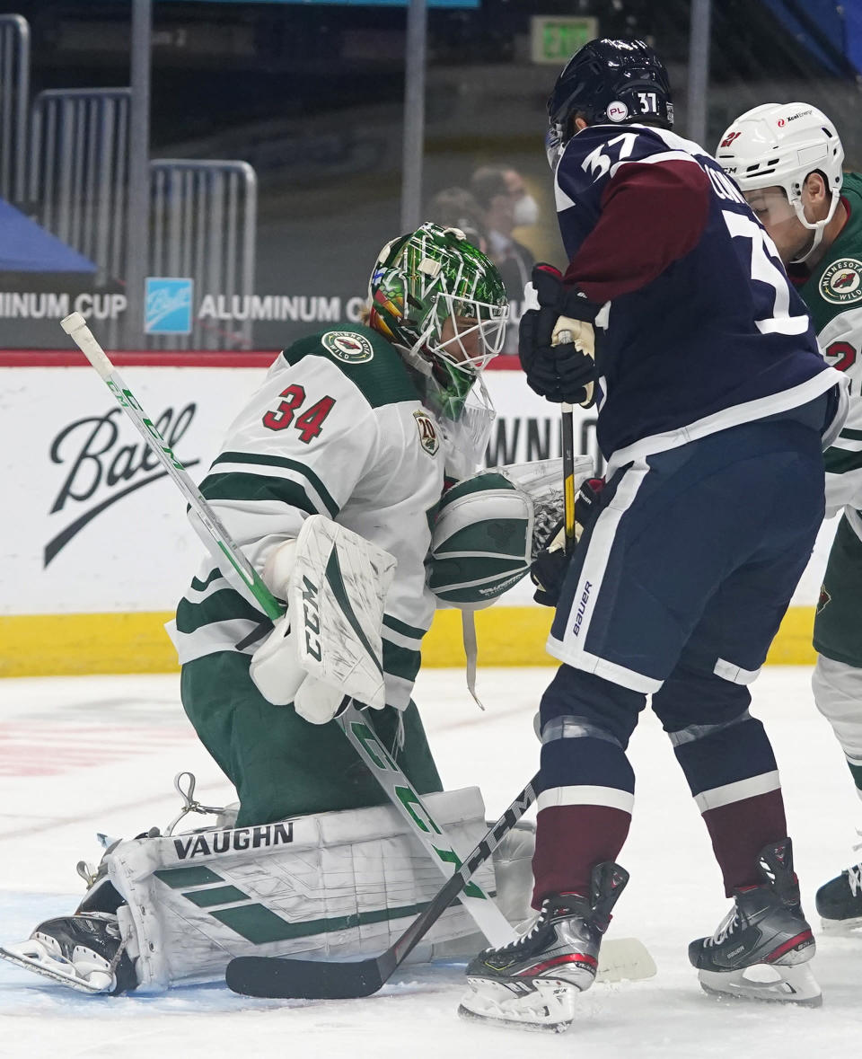Minnesota Wild goaltender Kaapo Kahkonen, left, makes a stop of a shot off the stick of Colorado Avalanche left wing J.T. Compher in the first period of an NHL hockey game Wednesday, Feb. 24, 2021, in Denver. (AP Photo/David Zalubowski)