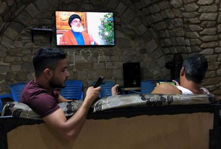 Men watch Lebanon's Hezbollah leader Sayyed Hassan Nasrallah speak on TV inside a coffee shop in Sidon