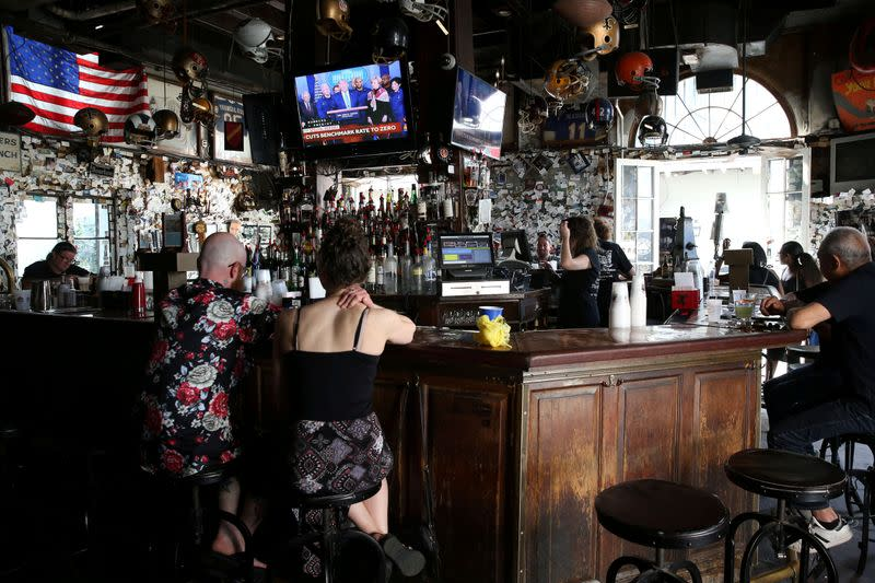 People watch U.S. President Donald Trump speak on a television inside a Bourbon St. bar in New Orleans