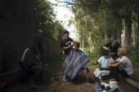 Yassime, 29, from Morocco cuts the hair of Ibrahim, 22, also from Morocco outside the Las Raices camp in San Cristobal de la Laguna, in the Canary Island of Tenerife, Spain, Friday, March 19, 2021. While Spain has been critical of its European neighbours' lack of solidarity when it comes to sharing the responsibility of migration, the country is similarly being criticized by migrants, authorities and human rights organizations on the Canary Islands where some 23,000 people arrived by sea last year and where many thousands remain on the island forcefully. (AP Photo/Joan Mateu)