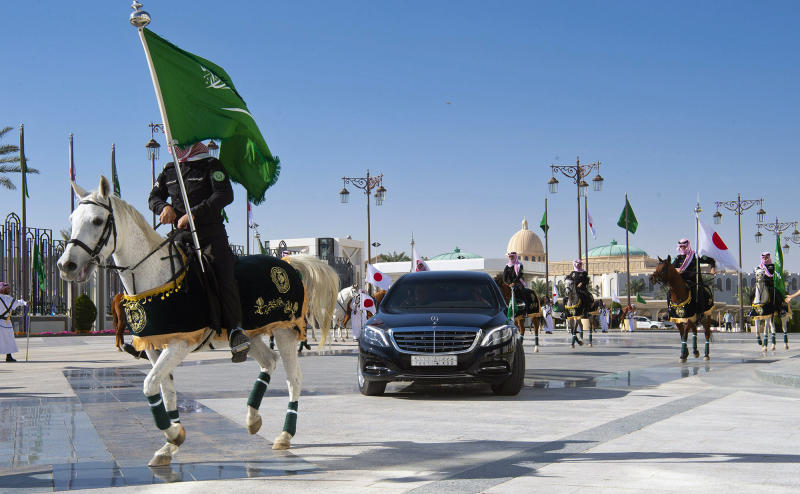 In this photo released by the Saudi Royal Palace, the convoy of Japan's Prime Minister Shinzo Abe, is surrounded by honor guards as he arrives at the Royal palace to meet with Saudi King Salman, in Riyadh, Saudi Arabia, Sunday, Jan. 12, 2020. (Bandar Aljaloud/Saudi Royal Palace via AP)