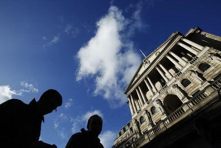 People pass the Bank of England in the City of London