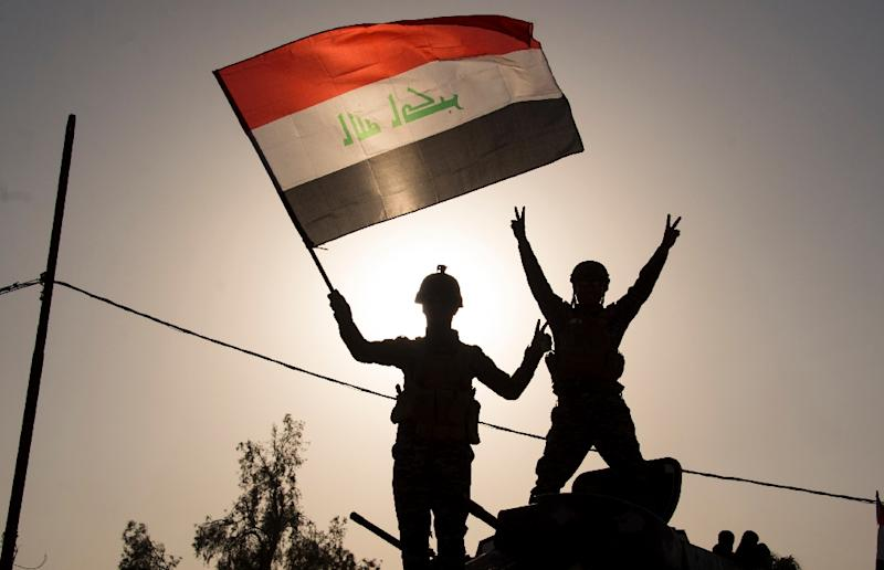 "Federal police wave the Iraqi flag as they celebrate in the Old City of Mosul on July 9, 2017 after the government's announcement of the ""liberation"" of the embattled city (AFP Photo/FADEL SENNA)"