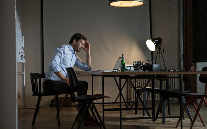 A stock photo of a businessman working late in an office - Westend61