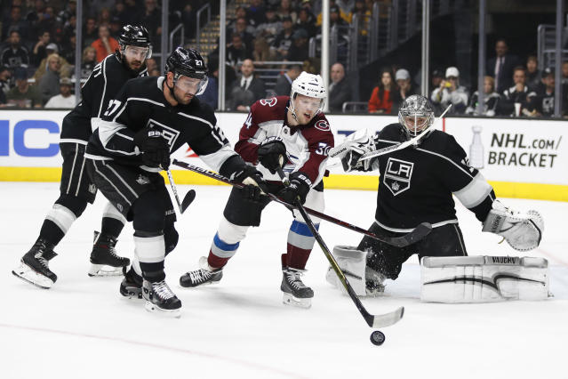 Colorado Avalanche's Carl Soderber, center, reaches for the puck under pressure by Los Angeles Kings' Alec Martinez, left, as Kings goalie Jonathan Quick, right, watches during the first period of an NHL hockey game Monday, April 2, 2018, in Los Angeles. (AP Photo/Jae C. Hong)
