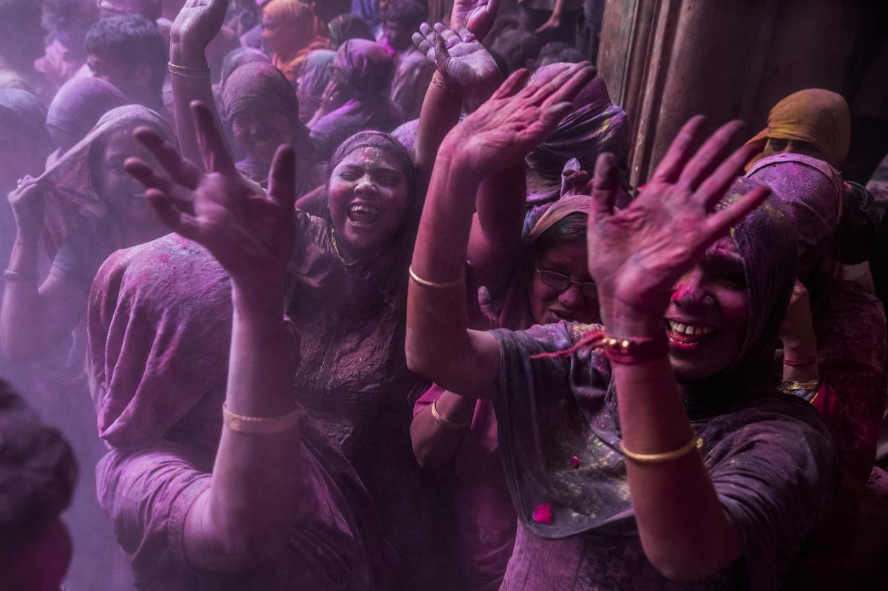 VRINDAVAN, INDIA - MARCH 27: Hindu devotees play with colour during Holi celebrations at the Banke Bihari temple on March 27, 2013 in Vrindavan, India. The tradition of playing with colours on Holi draws its roots from a legend of Radha and the Hindu God Krishna. It is believed that young Krishna was jealous of Radha's fair complexion since he himself was very dark. After questioning his mother Yashoda on the darkness of his complexion, Yashoda, teasingly asked him to colour Radha's face in which ever colour he wanted. In a mischievous mood, Krishna applied colour on Radha's face. The tradition of applying color on one's beloved is being religiously followed till date. (Photo by Daniel Berehulak/Getty Images)