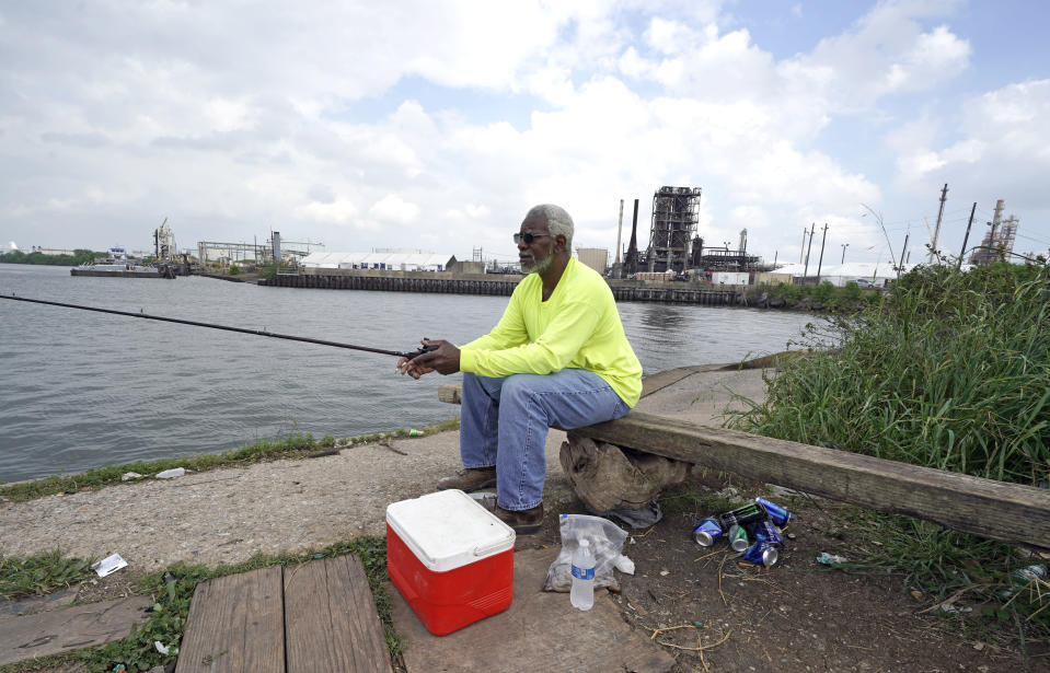 James Jackson fishes along the Houston Ship Channel Monday, March 23, 2020, in Houston. (AP Photo/David J. Phillip)