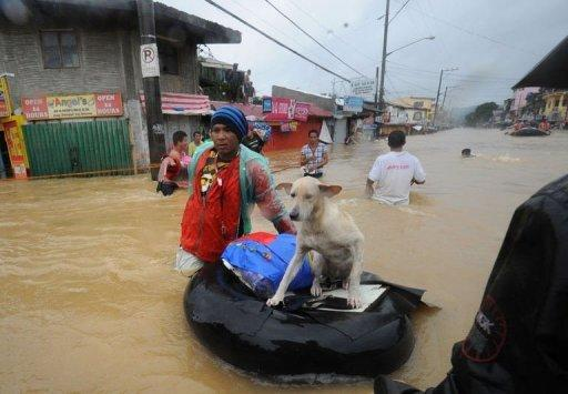 A resident pushes an improvised inflatable boat loaded with his dog through flood waters as they head for a safer area in the village of Tumana, Marikina town, in suburban Manila on August 7, 2012, after torrential rains inundated most of the capital