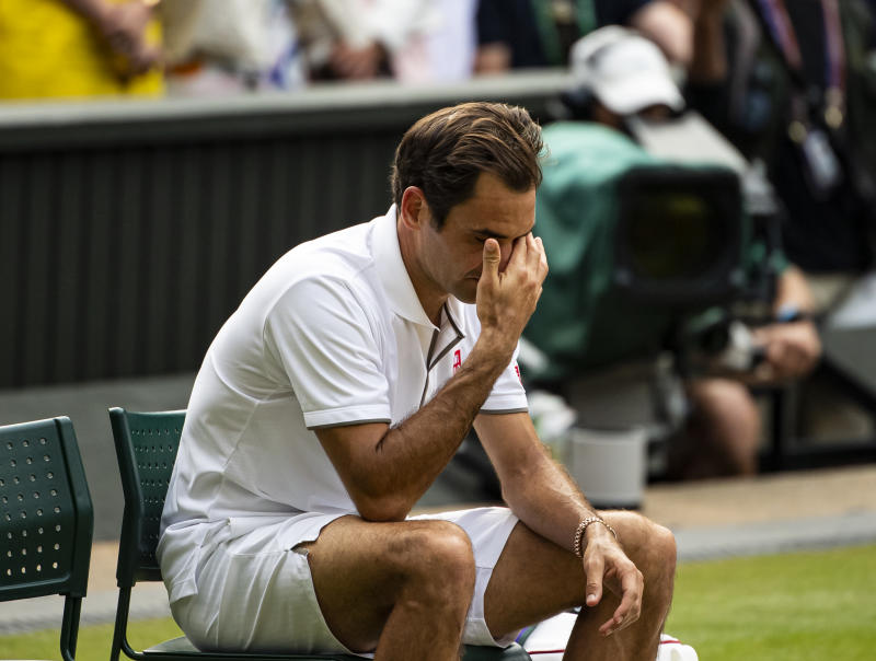 Roger Federer covers his face and looks dejected after losing.