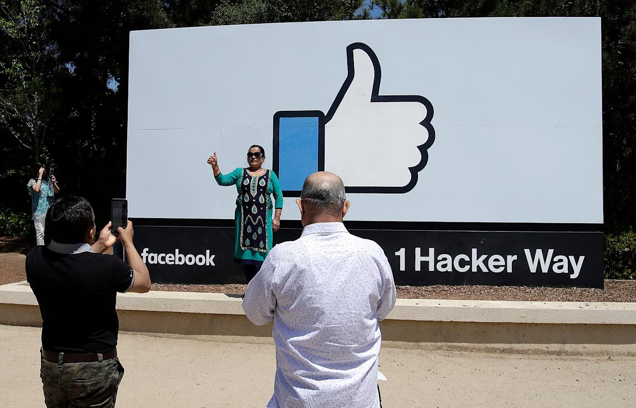 Visitors take photos in front of a sign at Facebook headquarters in Menlo Park, Calif., Thursday, April 25, 2019.