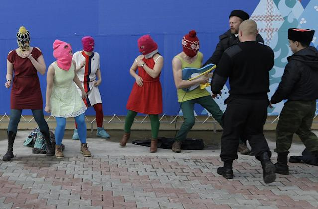 Members of the punk group Pussy Riot, including Nadezhda Tolokonnikova in the blue balaclava and Maria Alekhina in the pink balaclava, are attacked by Cossack militia and a Russian security officer in Sochi, Russia, on Wednesday, Feb. 19, 2014. The group had gathered in a downtown Sochi restaurant, about 30km (21miles) from where the Winter Olympics are being held. They ran out of the restaurant wearing brightly colored clothes and ski masks and were set upon by about a dozen Cossacks, who are used by police authorities in Russia to patrol the streets