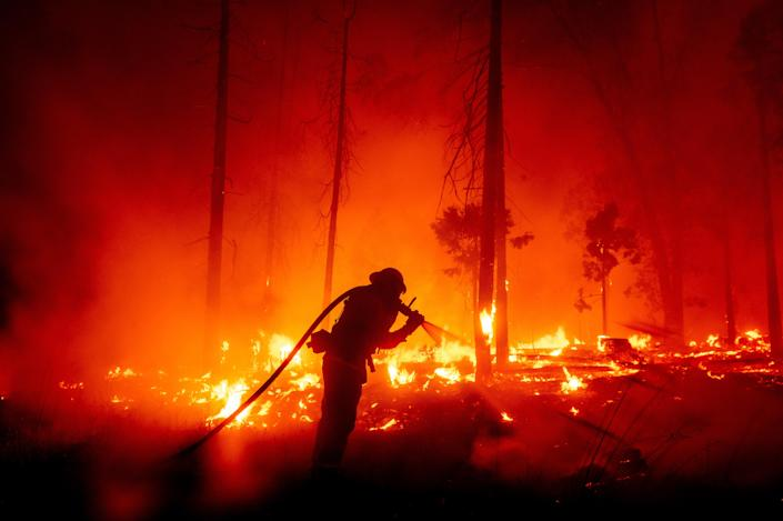 A firefighter battles the Creek Fire as it threatens homes in the Cascadel Woods neighborhood of Madera County, Calif ((Noah Berger via AP))