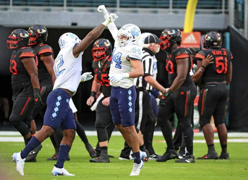 North Carolina linebackers Tomon Fox (12) and Jeremiah Gemmel (44) celebrate a stop against Miami during the first half of an during an NCAA college football game at Hard Rock Stadium In Miami Gardens, Fla, Saturday, Dec, 12, 2020. (Al Diaz/Miami Herald via AP)