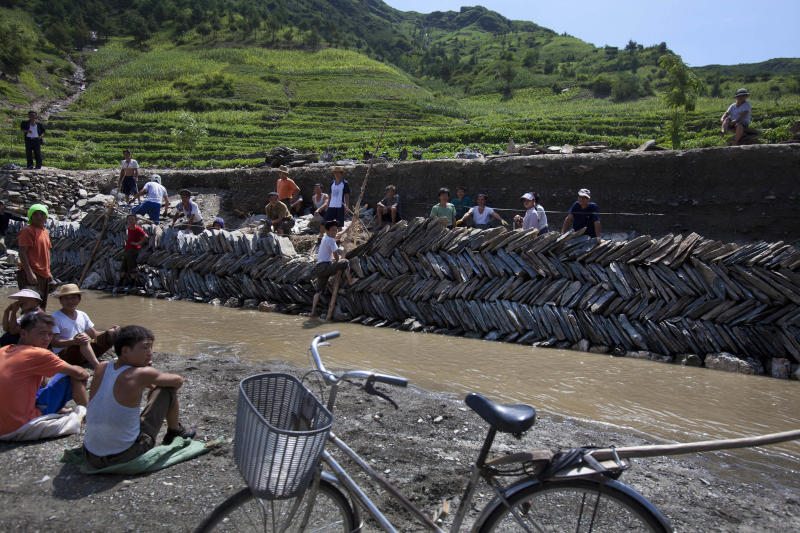 In this Monday, Aug. 13, 2012 photo, North Koreans try to rebuild the riverbank by hand which was destroyed by July flooding in Songchon County, North Korea. Twin typhoons are renewing fears of a humanitarian crisis in North Korea, where poor drainage, widespread deforestation and fragile infrastructure can turn even a routine rainstorm into a catastrophic flood. (AP Photo/David Guttenfelder)