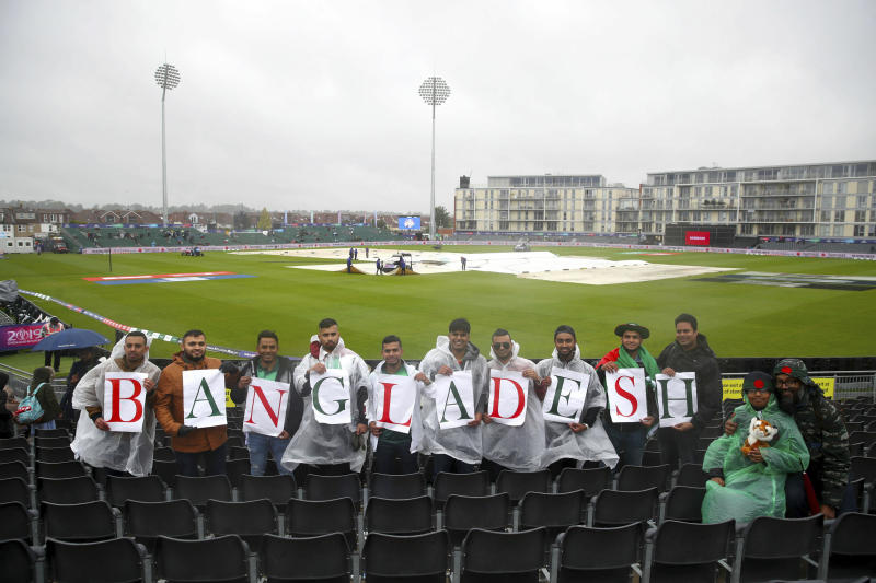 Bangladesh cricket fans display their allegiance, as they stand in the rain during the ICC Cricket World Cup group stage match at the County Ground in Bristol. England, Tuesday June 11, 2019.  Bangladesh is scheduled to play Sri Lanka Tuesday but there has not been any play yet, as much of England is suffering from unseasonal downpours. (Nick Potts/PA via AP)